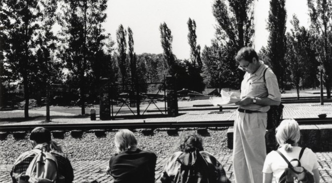 Sir Martin reading to his group of students at the railway line at Birkenau, just in front of the entrance gate and ruins of Crematorium III, June 1996